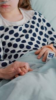 Close-up de uma mãe segurando as mãos de uma filha doente, esperando o tratamento de uma doença