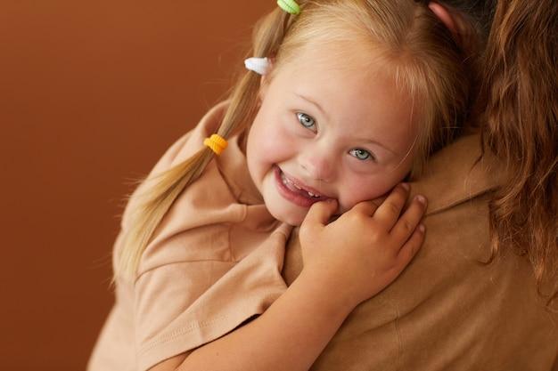 Close-up de uma mãe segurando uma filha feliz com síndrome de down enquanto fica de pé contra uma superfície marrom lisa no estúdio