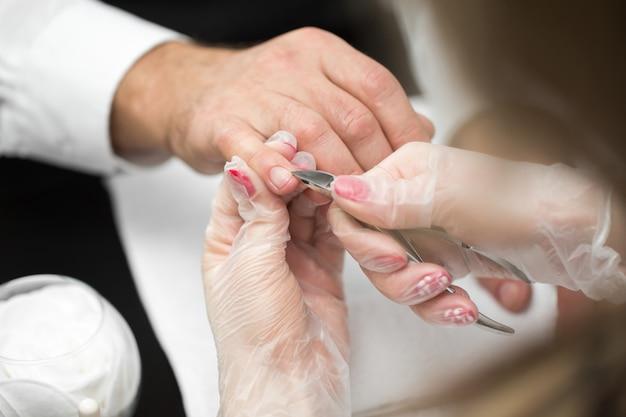 Close-up de uma manicure cortando a cutícula dos dedos da pessoa