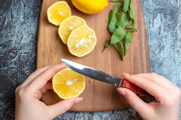 Close-up de uma mão cortando limões frescos e hortelã em uma tábua de madeira em fundo escuro