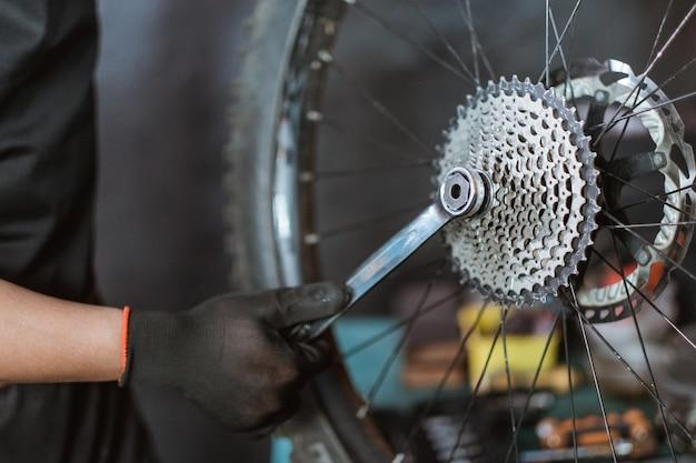 Close-up de uma mão de mecânico em luvas instalando uma roda dentada usando uma chave inglesa