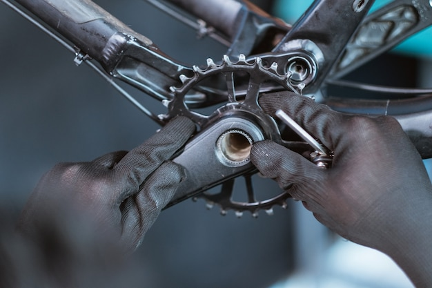 Close up de uma mão de mecânico usando luvas instalando o braço da manivela direito no suporte inferior