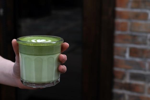 Close-up de uma mão de mulher e chá matcha. o garçom traz bebida.