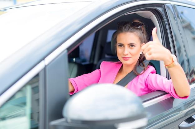 Close-up de uma mão de mulher mostrando um sinal de positivo com as janelas do carro.