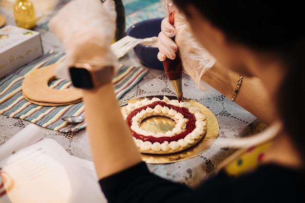 Close-up de uma mão de pastelaria decorando um pão de mel de natal com um saco de confeitar, vista por cima do ombro. ambiente de trabalho