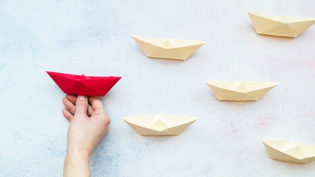 Close-up de uma mão de pessoa segurando o barco vermelho entre os barcos de papel branco no pano de fundo texturizado azul