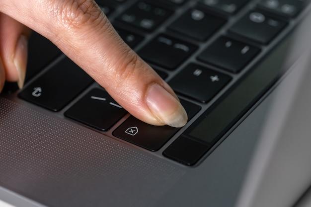 Close-up de uma mão feminina pressionando a tecla backspace para excluir em um teclado de laptop