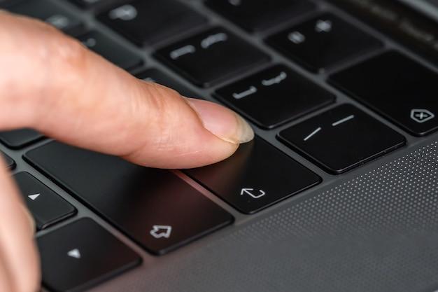 Close-up de uma mão feminina pressionando o botão enter em um teclado de laptop