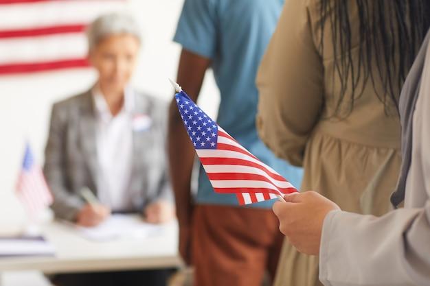 Close-up de uma mão feminina segurando a bandeira americana contra a superfície da assembleia de voto no dia das eleições, copie o espaço