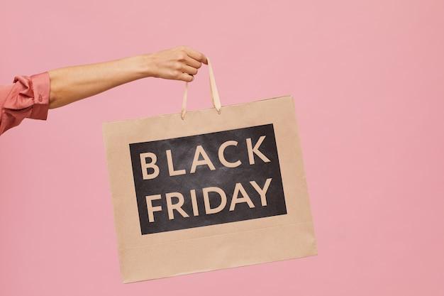 Close-up de uma mão feminina segurando a sacola de compras da black friday contra o fundo rosa