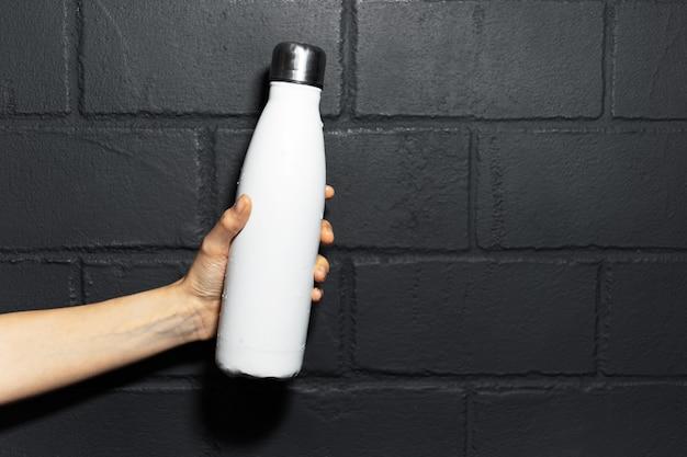 Close-up de uma mão feminina, segurando uma garrafa de água térmica de aço de cor branca, no fundo da parede de tijolo preto.