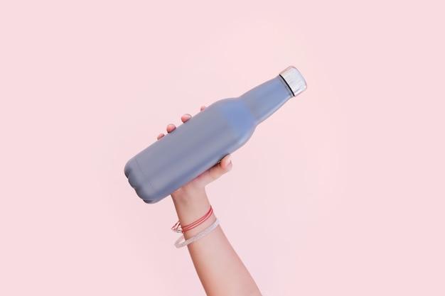 Close-up de uma mão feminina segurando uma garrafa de água térmica de aço inoxidável reutilizável eco no fundo de cor rosa pastel.