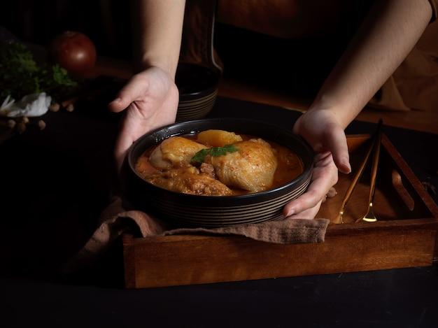 Close-up de uma mão feminina segurando uma tigela de frango