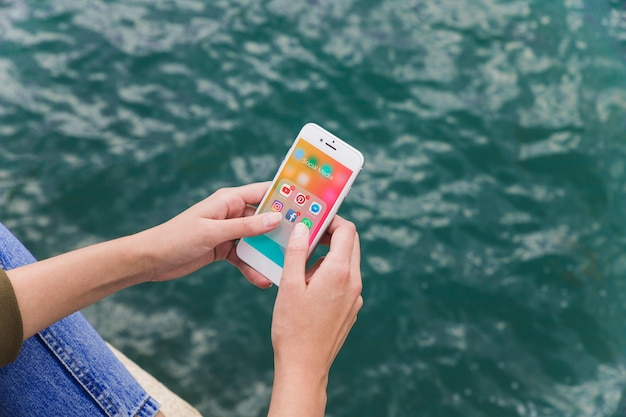 Close-up de uma mão feminina usando celular com notificações de mídia social na tela