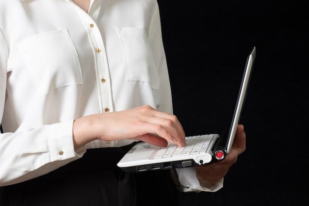Close-up de uma mão feminina usando um computador laptop e tocando a tela, isolada no fundo preto.