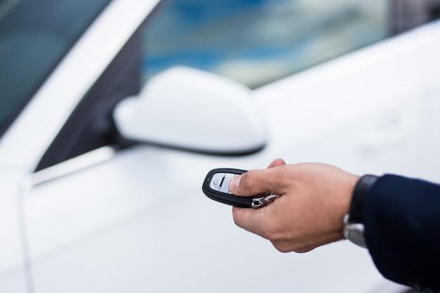 Close-up de uma mão masculina abrindo a porta do carro com um controle remoto