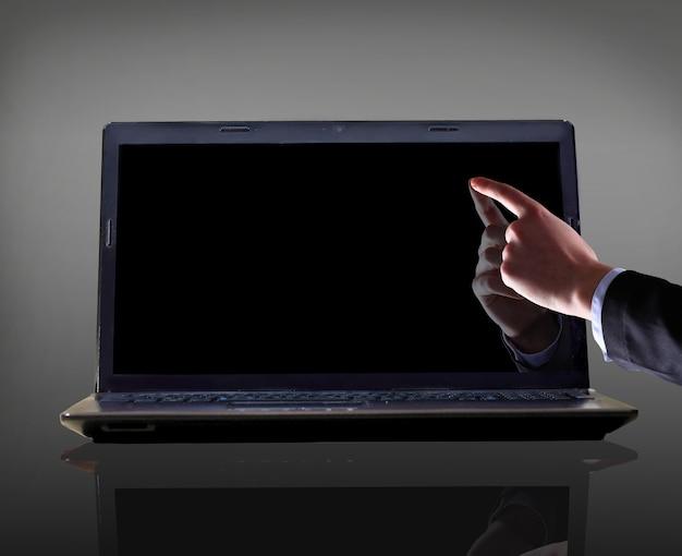 Close-up de uma mão masculina com o dedo indicador apontando para a tela do laptop sobre fundo preto