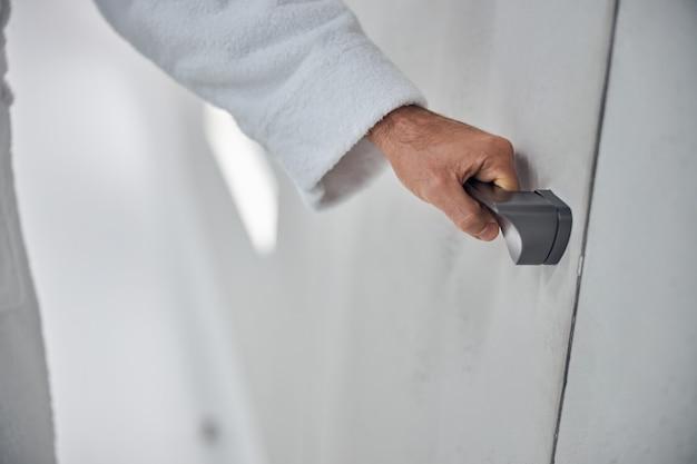 Close-up de uma mão masculina segurando a maçaneta prateada da porta na clínica de bem-estar