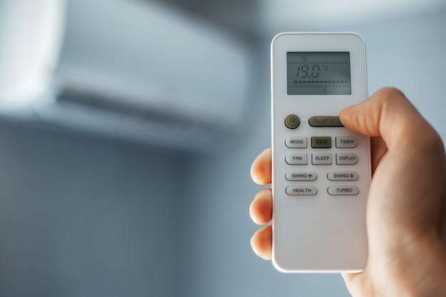 Close-up de uma mão masculina segurando o controle remoto do ar condicionado.