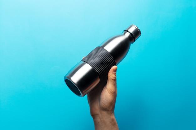 Close-up de uma mão masculina segurando uma garrafa de água reutilizável de aço contra a parede azul.