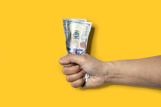 Close-up de uma mão segurando duas notas de dólar enrugadas. notas de dólar amassadas causam sinais de enrugamento. isolado em fundo amarelo e traçado de recorte.