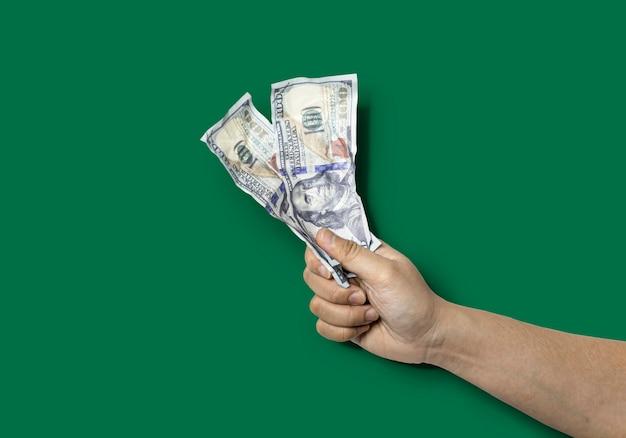 Close-up de uma mão segurando duas notas de dólar enrugadas. notas de dólar amassadas causam sinais de enrugamento. isolado sobre fundo verde e traçado de recorte.