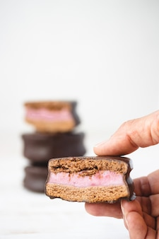 Close-up de uma mão segurando um biscoito coberto de chocolate com recheio. biscoitos de sanduíche.