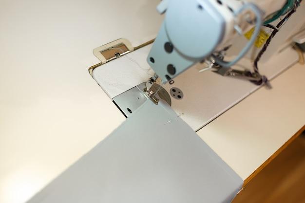 Close-up de uma máquina de costura com luz acesa e item de pano, alfaiate no local de trabalho, indústria de costura