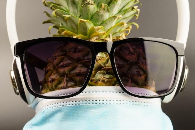 Close-up de uma máscara médica azul, óculos escuros e fones de ouvido, vestidos contra um abacaxi, sobre um fundo cinza