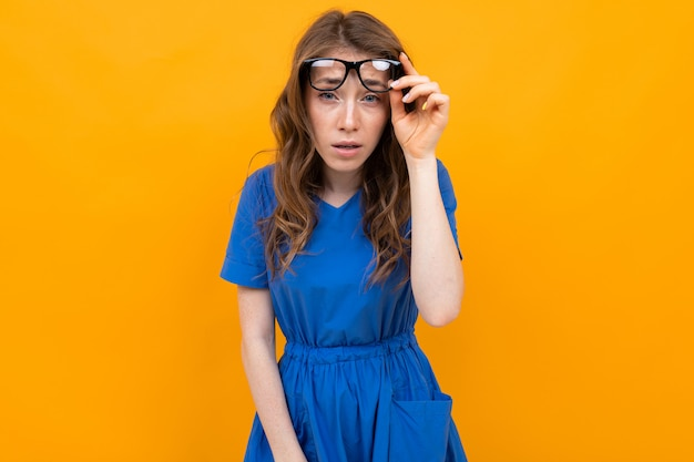 Close-up de uma menina de óculos com os olhos fechados em um fundo amarelo studio