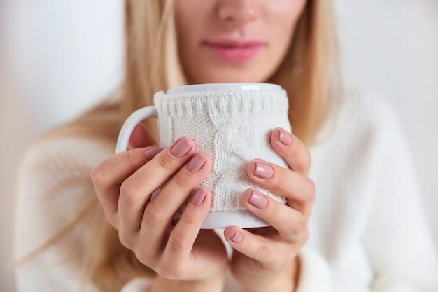 Close-up de uma menina loira com um suéter branco com uma caneca de chá quente nas mãos, abraça o estilo