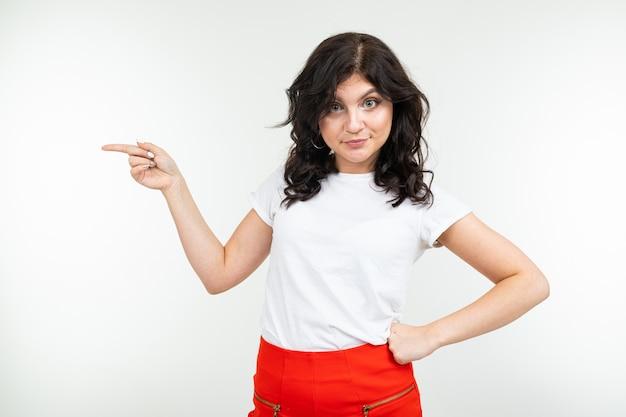 Close-up de uma menina morena em uma camiseta branca com as mãos sobre um fundo branco do estúdio