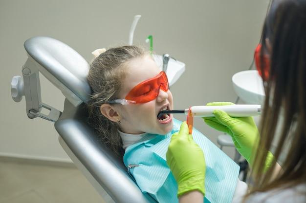 Close-up de uma menina paciente no dentista o médico está fazendo obturações dentárias