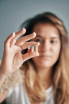 Close-up de uma menina segurando 3 comprimidos coloridos na mão