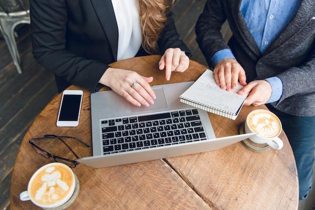 Close-up de uma mesa de centro com dois colegas sentados segurando um caderno e digitando no laptop