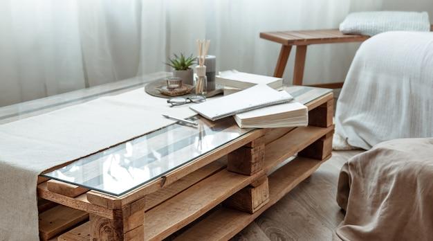 Close-up de uma mesa de madeira com livros em uma sala em estilo escandinavo.