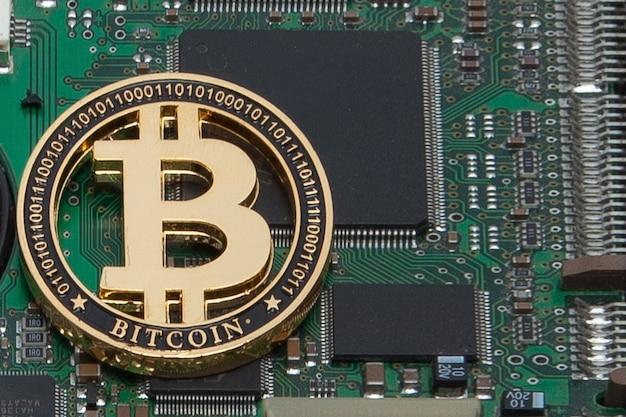 Close-up de uma moeda de ouro, processador de bitcoin de placa de circuito de computador e microchips.