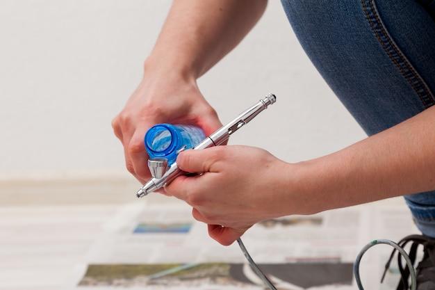 Close-up de uma mulher artista em jeans limpa e prepara o aerógrafo para o trabalho de pintar as paredes.
