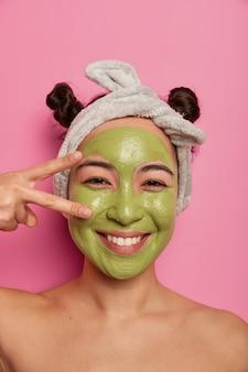 Close up de uma mulher asiática natural se diverte durante os procedimentos de beleza, faz o sinal da paz sobre os olhos, aplica máscara facial purificadora verde, limpa a pele, fica com o corpo nu isolado na parede rosa