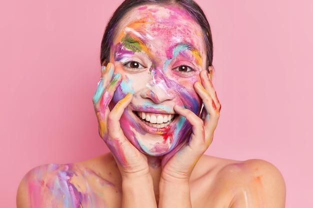 Close-up de uma mulher asiática positiva pintada com tintas coloridas de guache mantendo as mãos no rosto e sorrisos felizes