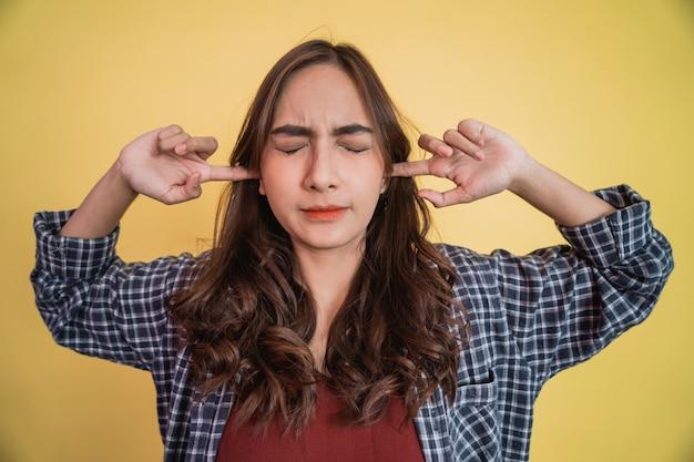 Close-up de uma mulher atraente cobrindo as orelhas com os dedos e fechando os olhos