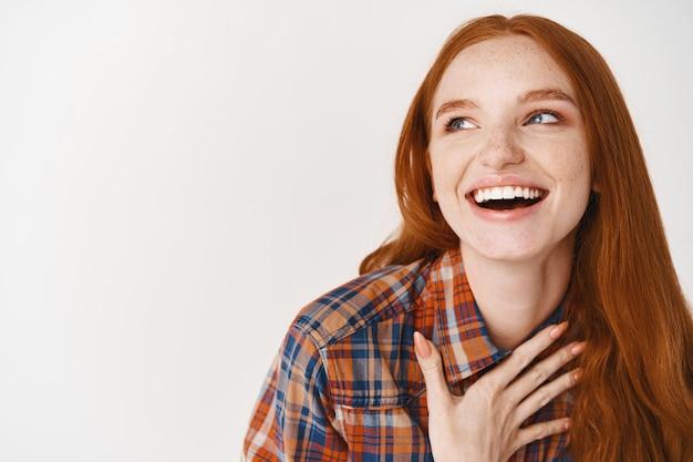 Close-up de uma mulher bonita com cabelo ruivo e pele pálida rindo feliz, segurando a mão no coração e olhando para a esquerda para o logotipo, em pé sobre a parede branca
