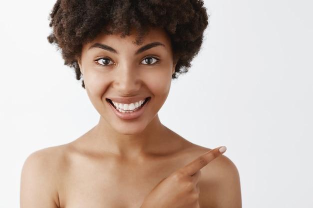 Close-up de uma mulher bonita e atraente feminina nua de pele escura com penteado encaracolado apontando para o canto superior direito e sorrindo alegremente ajudando a encontrar o caminho