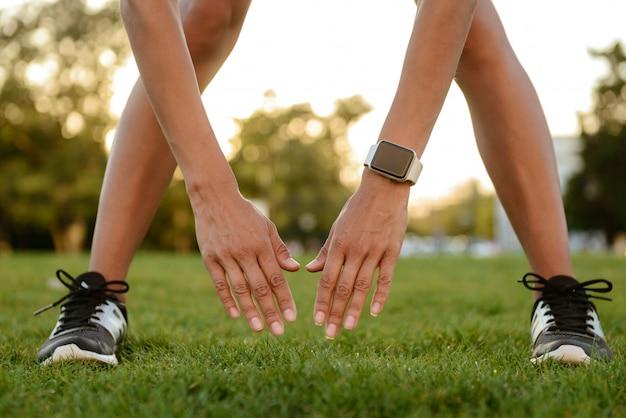 Close-up de uma mulher braços e pernas fazendo alongamento