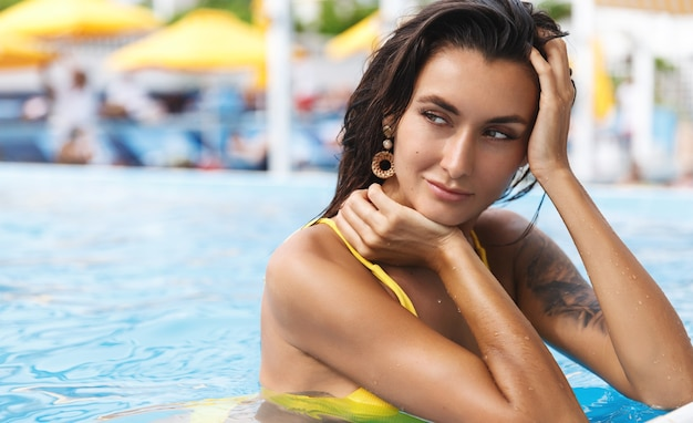 Close-up de uma mulher bronzeada com uma tatuagem no ombro, borda magra da piscina, se virando com um sorriso sedutor e relaxado.