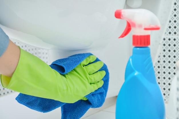 Close-up de uma mulher com as mãos nas luvas com pano e detergente para lavar roupa pendurada no vaso sanitário, limpeza doméstica no banheiro