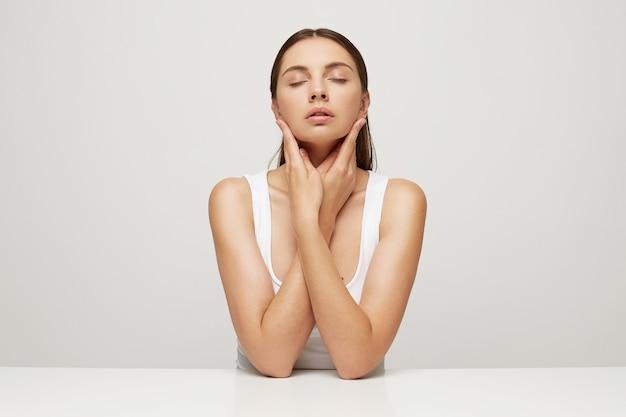 Close-up de uma mulher com pele fresca e saudável perfeita sentada à mesa, mãos cruzadas e tocando o rosto