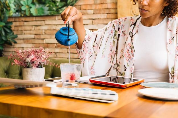 Close-up de uma mulher com tablet digital; amostras de cores na mesa derramando a água no copo