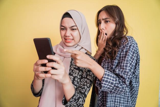 Close-up de uma mulher com um lenço na cabeça e uma mulher com cabelo comprido estão usando um telefone celular e são surpreendidos ...