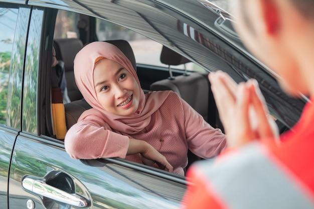 Close-up de uma mulher com um véu com um carro chegando à oficina para ser saudada por um mecânico